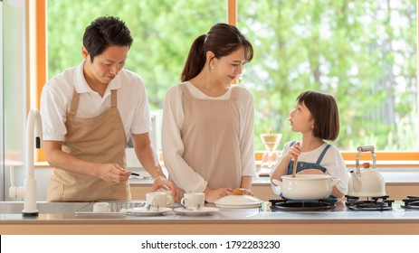 little asian girl and parents cooking at kitchen