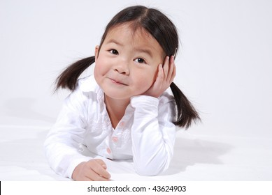 little asian girl with pig tails in a white dress