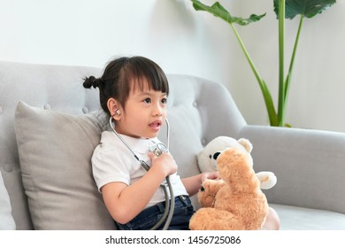 Little asian girl play with baby doll toy.Little asian girl hold stethoscope in hand and check baby doll toy.