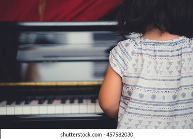 Little asian girl play piano at home, Child development.Selective focus
