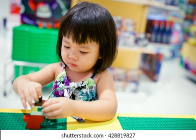 Little asian girl playing with colorful toy blocks. Kids play with educational toys at kindergarten or day care. Preschool children build tower with plastic block. Toddler kid in nursery.