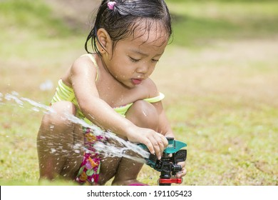 Little asian girl playing with a garden sprinkler.