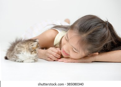 Little Asian girl playing with lovely Persian kitten on isolated