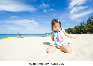 Little asian girl playing on beach.