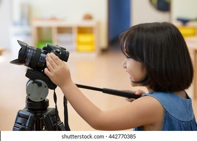 Little Asian girl practices for taking photo with digital camera on tripod