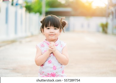 Little asian girl pray and wishing you a happy Chinese New Year.