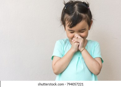 Little asian girl praying on white background. Children asia hand pray. press the hands together at the chest or forehead in sign of respect.  Faith spirituality and religion concept.