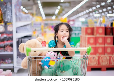 little asian girl in princess costume sitting with dolls in the cart between shopping