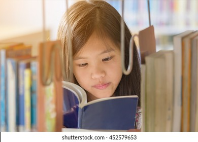 Little Asian girl reading a book in library at school