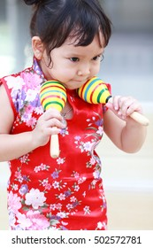 Little asian girl  red chinese dress holding the musical instrument