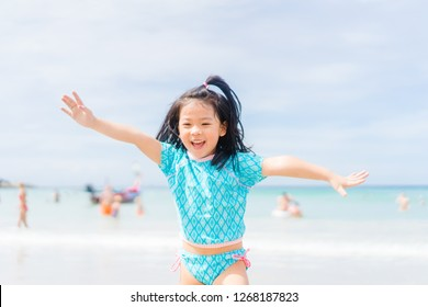 Little asian girl running on sea sand on the beach.Vacation and relax concept.Playful active kid on beach in summer vacation.