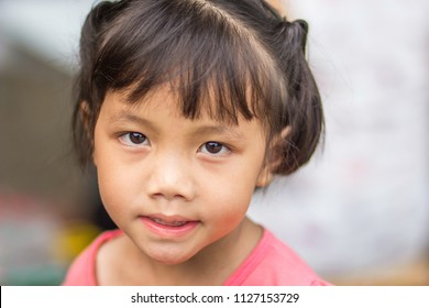 Little Asian girl with sharp eyes in pink shirt