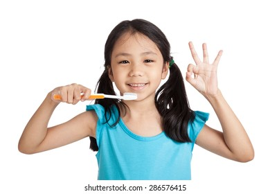 Little asian girl show OK with toothbrush  isolated on white background