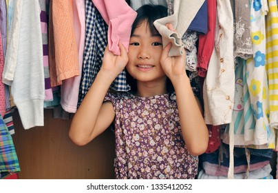 A little asian girl is sitting in a closet of messy clothes. Cute asian kid plays in her wardrobe.