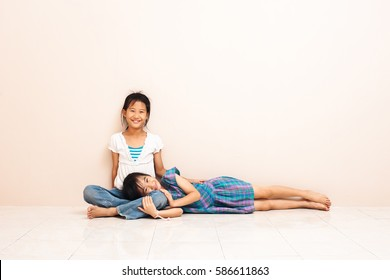 Little asian girl sitting with her old sister on floor at home. lovely relation between siblings.