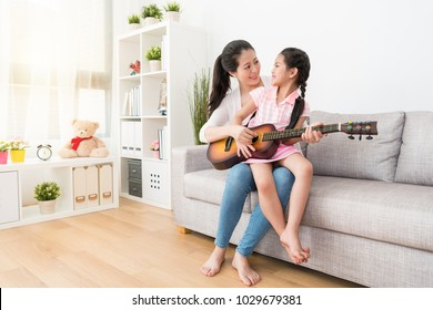 Little asian girl sitting on mother's leg and hod a guitar. They look into each other's eyes. Love concept. They have warm joyful leisure time in the weekend.
