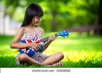 Little asian girl sitting on grass and play ukulele, Outdoor portrait