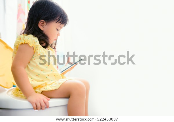 Little asian girl sitting on a toilet and holding smartphone.Training child concept.