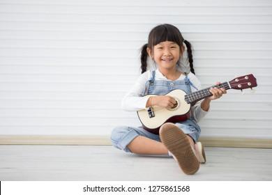 little asian girl sitting playing ukulele on white background with copy space