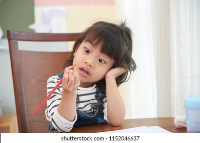 Little Asian girl sitting at table with papers and looking at colored pencil with amazement and confusion