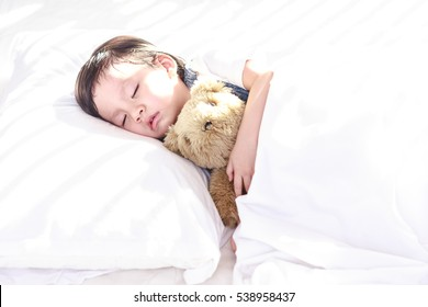 Little asian girl sleeping with her toy teddy bear on the bed, New family and baby healthy concept