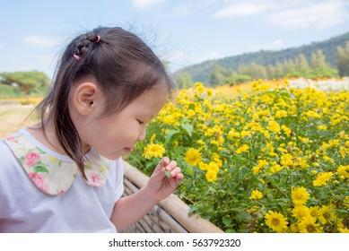 Little asian girl smelling flower in garden