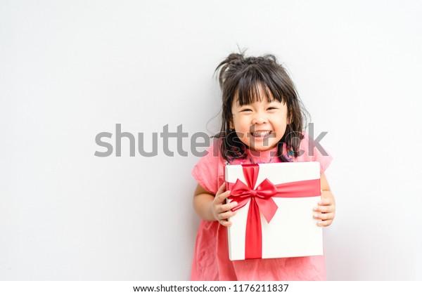 Kleine aziatische meisje glimlach en opgewonden en het houden van rode geschenkdoos op witte achtergrond.kind houden geschenkdoos in Kerstmis en Nieuwjaar concept.