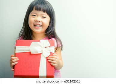 Little asian girl smile and holding red gift box on white background.child holding gift box.