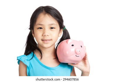 Little asian girl smile with piggy bank  isolated on white background