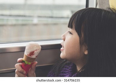 Little asian girl smiling  and eating ice cream.She travels on a train,vintage filter