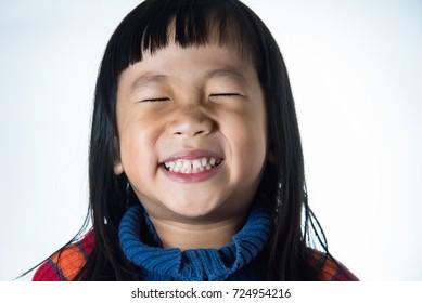 Little Asian Girl Smiling On White Background.