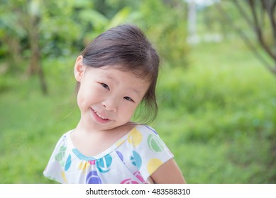 Little asian girl smiling in park