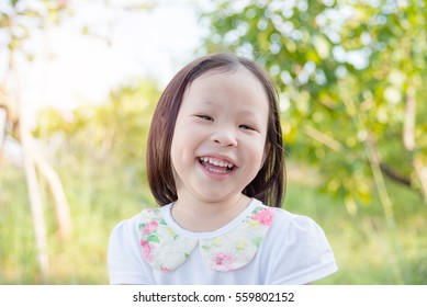 Little asian girl smiling in park