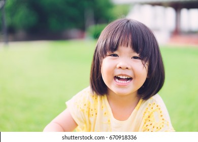 Little asian girl smiling with perfect smile and white teeth in a park and looking at camera.Little girl child showing front teeth with big smile.Joyful portrait of asian elementary school student.
