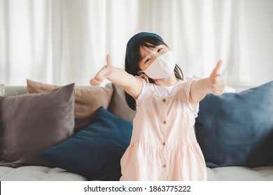 kleines asiatisches Mädchen, das mit einer Gesichtsmaske zum Schutz vor Coronavirus lächelt, zeigt die Daumen-up Geste zu Hause. Soziale Distanzierung und neues Normalkonzept