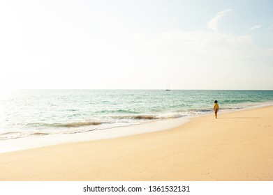 A little asian girl standing while relaxing on the sunset beach, summer sun shines on white sand beach and yacht in the tropical sea. Tai Muang Beach, Phang Nga, Thailand.