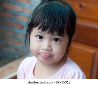 little asian girl sticking tongue out