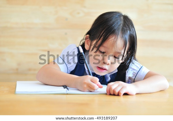 little asian girl study and writing a notebook with pencil smile face
