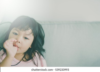 Little asian girl sucking thumb on sofa.