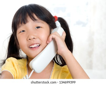 Little asian girl talking on the phone