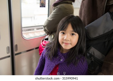 Little asian girl travels on a train