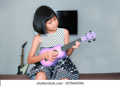 little Asian girl trying to play ukulele with fully happiness moment.