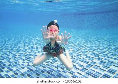 little asian girl underwater in swimming pool