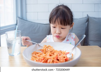 Little asian girl with unhappy face while having fried spaghetti with tomato sauce for lunch ,picky eater child concept.