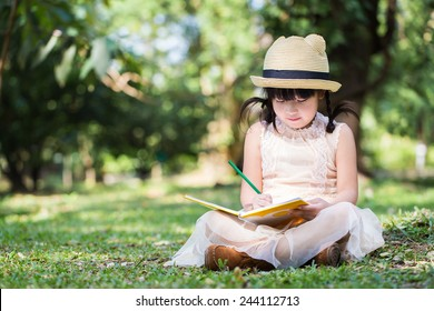 Little asian girl use pencil writing on notebook for writing book with smiling face in the park