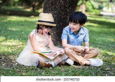Little asian girl use pencil writting on notebook for writing book with smiling face in the park and her brother looking to her