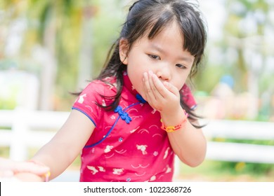 Little asian girl vomiting in the park.