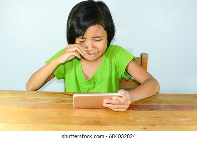 Little Asian girl watch movie on smartphone and crying , children with  technology and communication concept