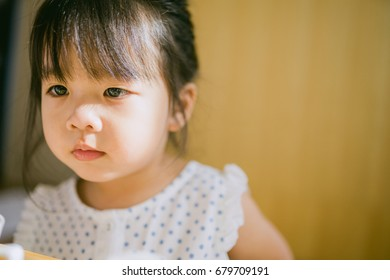Little asian girl watching TV in table.