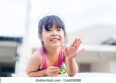 Little asian girl waving hand for good bye in the moon roof car.Concept: Bye Summer and go to school.Outdoor portrait: beautiful kid smiling and waving say good bye.